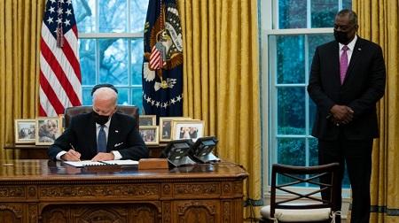 Le secrétaire américain à la Défense, Lloyd Austin, regarde le président Joe Biden signer un décret annulant l'interdiction d'une directive de l'ère Trump, le 25 janvier 2021. © AP