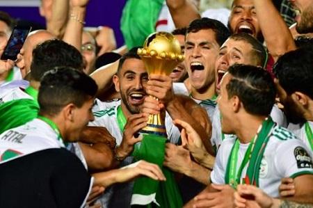 L'attaquant Riyad Mahrez (c) soulève le trophée après la victoire de l'équipe d'Algérie contre le Sénégal en finale de la CAN-2019, le 19 juillet 2019 au Caire AFP