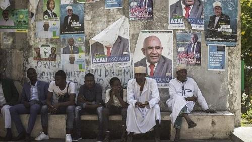 Des Comoriens patientent assis devant un mur couvert d'affiches de campagne pour la présidentielle, le 18 mars 2019. © GIANLUIGI GUERCIA / AFP