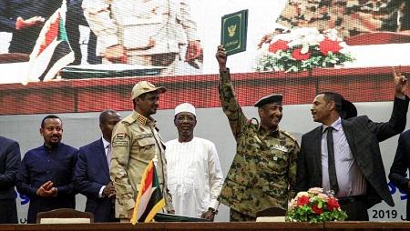 Ahmed al-Rabie, représentant de l'Alliance pour la liberté et le changement (D) et Mohammed Hamdan Daglo, le numéro deux du Conseil militaire (G en treillis), lors de la signature de l'accord le 17 août 2019 à Khartoum. © EBRAHIM HAMID / AFP