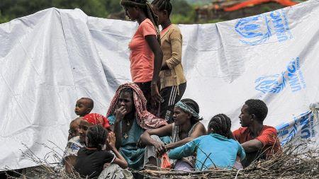 Des réfugiés éthiopiens du groupe ethnique Qemant sont assis à l'extérieur d'un abri de fortune dans le village de Basinga, dans le district de Basunda, dans la région orientale du Soudan - ASHRAF SHAZLY/AFP