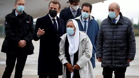 L'ex-otage française Sophie (G) à son arrivée sur le sol français entourée du président E.Macron (G) et du ministre Le Drian (D). GONZALO FUENTES / POOL / AFP