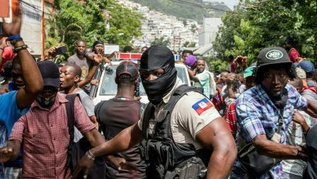 Une foule s'agglutine autour d'une voiture transportant des personnes suspectées d'être membre du commando ayant assassiné le président Jovenel Moïse. © VALERIE BAERISWYL/AFP