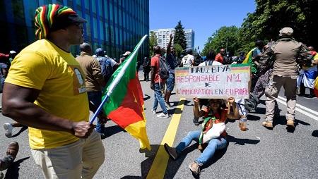 Une femme porte une banderole avec l'inscription «Paul Biya, premier responsable de l'immigration en Europe» lors d'une manifestation contre la présence du président camerounais Paul Biya à Genève, le 29 juin 2019. © FABRICE COFFRINI / AFP