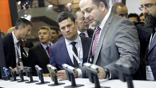 Le ministre brésilien de la Justice Sergio Moro regarde des armes au stand de l'entreprise Glock pendant le plus grand salon d'armement d'Amérique latine, à Rio de Janeiro, le 2 avril 2019. REUTERS/Ricardo Moraes