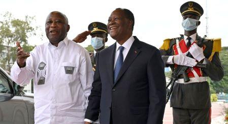Le président de la Côte d'Ivoire Alassane Ouattara (au centre) pose avec l'ancien président Laurent Gbagbo (à gauche) au palais présidentiel d'Abidjan, le 27 juillet 2021.