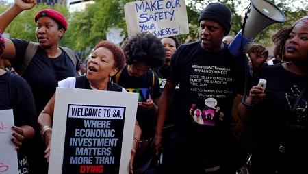 """Femme brandissant une pancarte lors d'une manifestation à la bourse de Johannesburg : """"Bienvenue en Afrique du sud, où les investissements économiques comptent plus qu'une mort."""" © REUTERS/Stringer"""