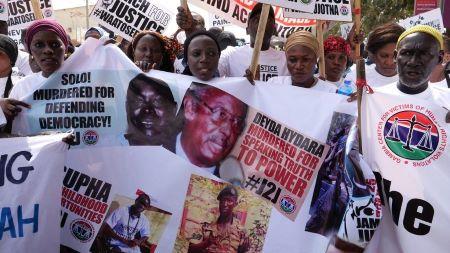 Des manifestants tiennent des bannières portant les visages de victimes du régime de Yahya Jammeh . ROMAIN CHANSON/AFP