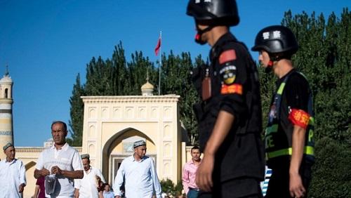 Des policiers chinois surveillent la sortie de la mosquée de Kashgar, dans la région de Xianjing où vit la minorité musulmane ouïghoure. (Image d'illustration) Johannes EISELE / AFP