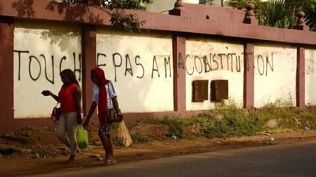 Deux femmes passent devant une inscription laissée par les opposants à une réforme de la Constitution, à Conakry. Carol Valade/RFI
