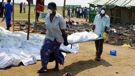 Des volontaires transportent les corps des 160 victimes, le 14 août 2004, au lendemain du massacre du camp de réfugiés de Gatumba. © AFP PHOTO SIMON MAINA