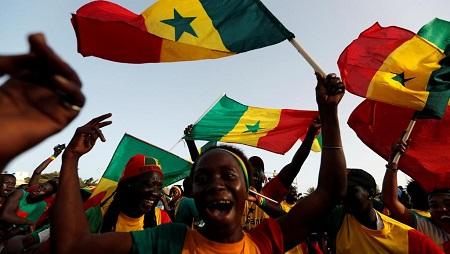 En Algérie, le pays se prépare à une grande fête ce vendredi soir pour la finale de la Coupe d'Afrique des nations. Mais malgré l'euphorie générale et même si les manifestations rassemblent moins de monde, les supporters restent mobilisés par le mouvement de protestation. Dans les rues, des vendeurs improvisent des stands pour vendre les maillots de l'équipe nationale. Les premiers supporters qui bénéficient du pont aérien ont décollé.  L'ambiance est à la fête, mais Samy, 32 ans, n'oublie pas le contexte politique. « Ce n'est pas avec une formule à 35 000 dinars pour aller au Caire supporter l'équipe nationale que je vais ensuite être contre le mouvement, ou avec Gaïd Salah » souligne-t-il. « Ils rendront des comptes devant Dieu. On espère que le pays s'améliorera et qu'on va bien le reconstruire. »  « L'article 7 et l'article 8. Puis ils s'en vont tous. Puis on les gagne tous »  Le président par intérim a fait le déplacement en Égypte. La ministre de la Culture a donné une interview, portant le maillot officiel de l'équipe. Cela fait rire Zoubir, qui a une liste de revendications très précises, à commencer par l'application de la Constitution : « L'article 7 et l'article 8. Puis ils s'en vont tous. Puis on les gagne tous. Et par la grâce de Dieu, on verra une nouvelle Algérie. Une Algérie meilleure et dont les Algériens seront fiers. Comme on le souhaite et comme le souhaitaient les martyrs de l'indépendance ».  On prie pour remporter cette coupe et durant la finale, durant le match nous continuerons de prier pour gagner. Le peuple algérien a besoin de cette victoire. Nous vivons actuellement un contexte difficile donc il nous faut cette victoire. Et nous montrerons au monde comment on célèbre une victoire de manière civilisée et pacifique.  Ecoutez ces supporters de l'Algérie avant la finale 19-07-2019 - Par Sami Boukhelifa   00:00  00:55 Parmi les chansons créées à l'occasion de la finale, certaines reprennent d'ailleurs les slogans de la contestation.