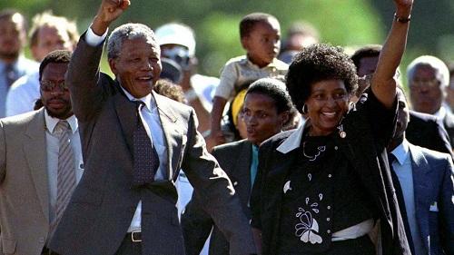 Nelson Mandela, levant le poing droit vers le ciel, tenant par l'autre main, son épouse Winnie, au sortir de la prison de Verster