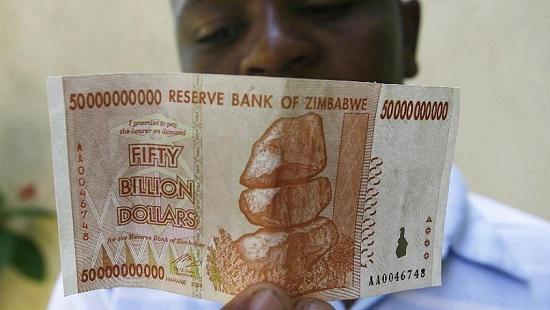 Un homme tient un billet de 50 milliards de dollars zimbabwéens en 2009. © AFP Photo/Desmond Kwande