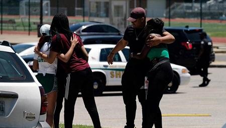 Un groupe de jeunes gens s'étreignent devant le lycée fréquenté par Brandon Webber, le jour où il a été abattu par un agent de police à Memphis, dans le Tennessee (États-Unis), le 12 juin 2019. REUTERS/Ricardo Arduengo