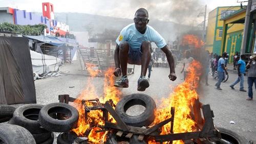 Un manifestant saute au-dessus d'une barricade en feu lors d'une manifestation à Port-au-Prince, le 10 février 2019. REUTERS/Jeanty Junior Augustin