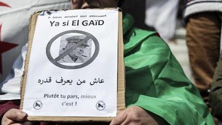 Un manifestant tient une pancarte demandant le départ du chef d'état-major Ahmed Gaïd Salah. © KENZO TRIBOUILLARD / AFP